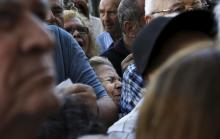 A pensioner (C) is squeezed as she waits outside a National Bank branch to receive part of her pension in Athens, Greece July 1, 2015. REUTERS/Alkis Konstantinidis